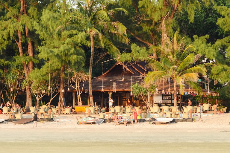 Koh Phayam, Thailand - January 9, 2016: Long beach or Aow yai beach in Koh Phayam, Thailand, touristic island, tourists sitting on the beach in low ti