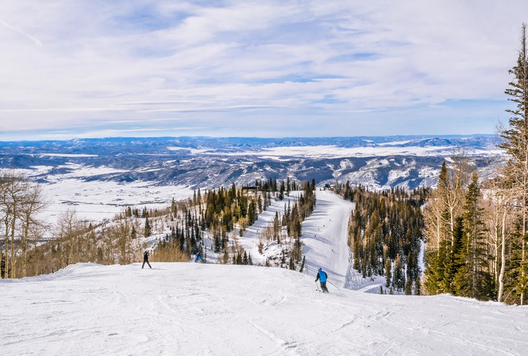 View of a Rocky Mountain ski slope; mountains and blue sky in the background