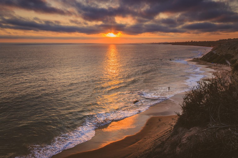 Magnificent coastline view of Crystal Cove beach at sunset with clouds in the sky Newport Beach, California