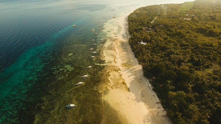 Aerial view of tropica Alona beach on the island Bohol, resort, hotels, Philippines. Beautiful tropical island with sand beach, palm trees. Tropical landscape. Seascape: Ocean, sky, sea. Travel concept.