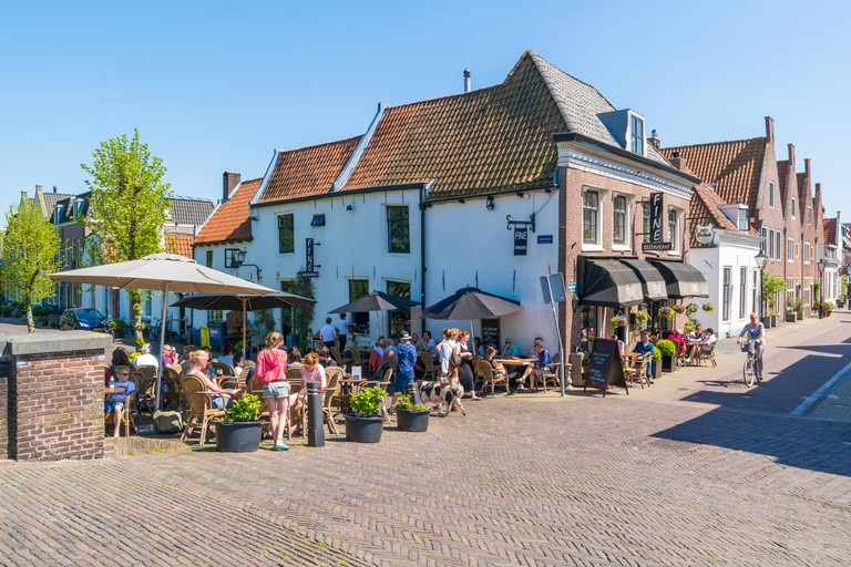 People relaxing on outdoor terrace of cafe on Oude Haven in old town of Naarden, North Holland, Netherlands