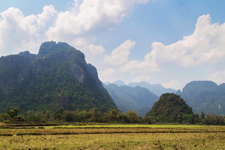 Scenic view of fields, limestone mountains and Pha Poak hill near Vang Vieng, Vientiane Province, Laos, on a sunny day.