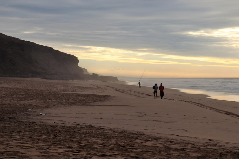 Two Runners on the beach at Plage Des Nations, with a Pole Fisherman Behind, Sunset and Dusk