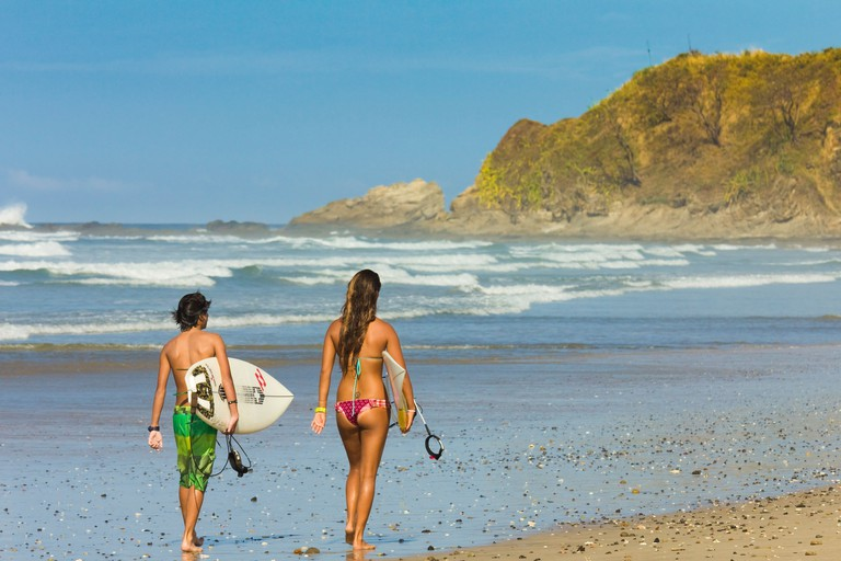 Boy and girl with surfboards at Playa Guiones beach, Nosara, Nicoya Peninsula, Guanacaste Province, Costa Rica, Central America