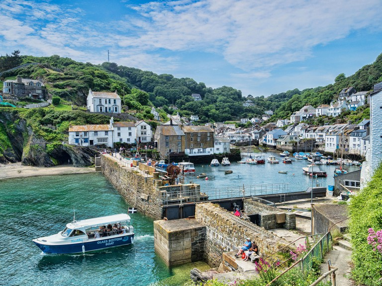Polperro, Cornwall, UK - One of the most beautiful villages in Cornwall, on an idyllic summer day, with a boat just leaving the harbour._PW6ACA