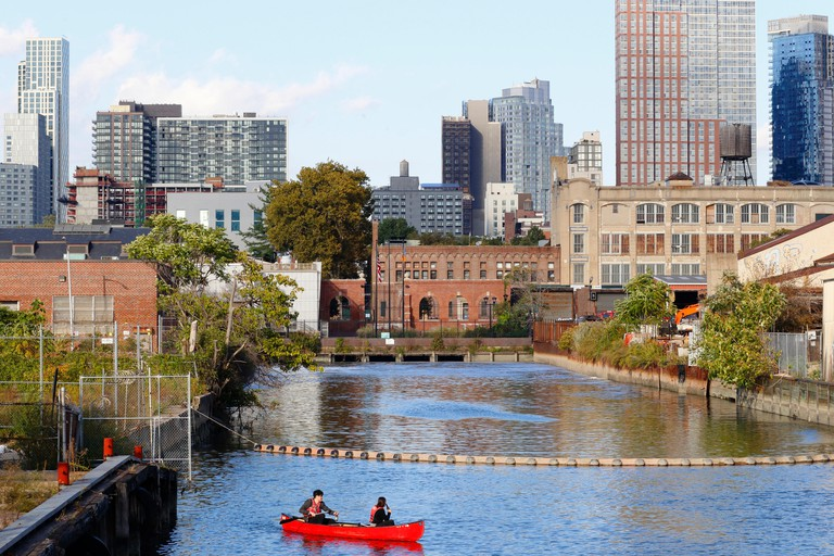 Weekend canoers on the Gowanus Canal enjoy beers with the Downtown Brooklyn/Fort Greene skyline in the background. Image shot 10/2018. Exact date unknown.