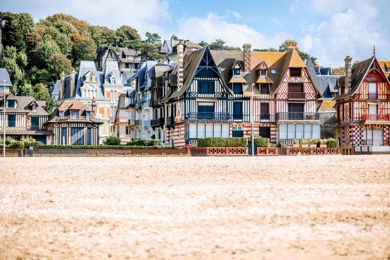 View on the cooastline with sandy beach and luxury buildings in Trouville, famous french town in Normandy - PY64X2