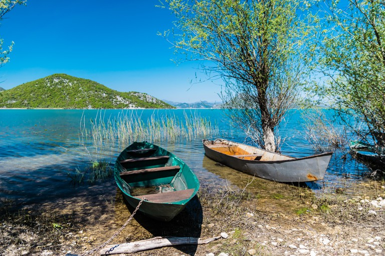 Two small vessels on an indigo tropical looking beach. Scenic view from Skadar Lake, Montenegro