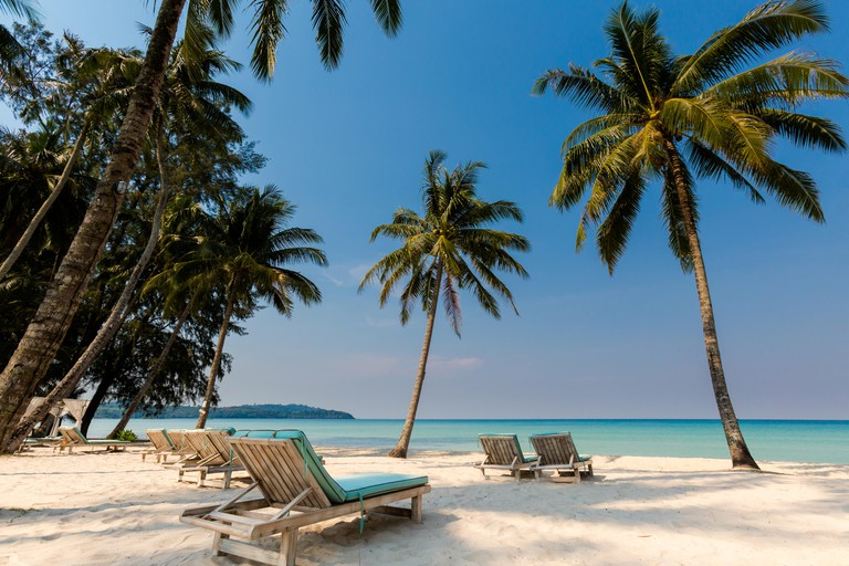 Summer landscape on tropical koh Kood island in Thailand. Panorama of white sand beach with coconut palms taken on Klong Chao.