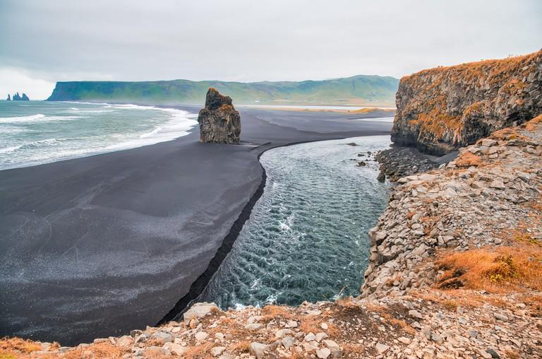 Reynisfjara Black Beach, Iceland. Rocks and vegetation in autumn season.