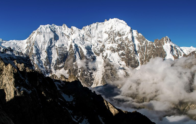 The view of north face of mount Dykh Tau in morning sunlight with a clear summit, in the mountains of the Russian Caucasus _