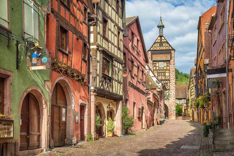 Central street of Riquewihr village with colorful traditional half-timbered french houses and Dolder Tower, Alsace_JEMM03