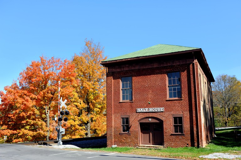 Historic Salt House sits besides railroad tracks in the old town of Jonesborough, Tennessee.  Autumn colors the trees around the Salt House.