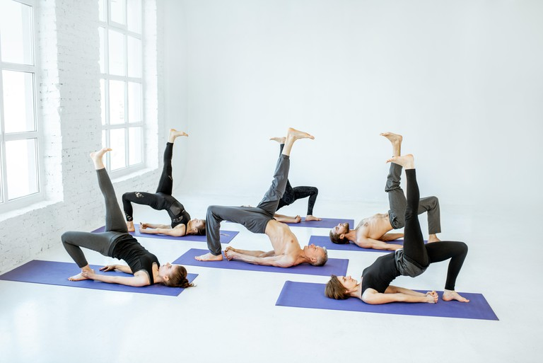 Group of athletic people keeping yoga pose during the training in the white studio