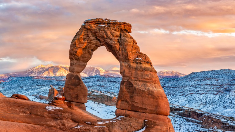 La Sal Mountains behind iconic Delicate Arch, Arches National Park, Moab, Utah.