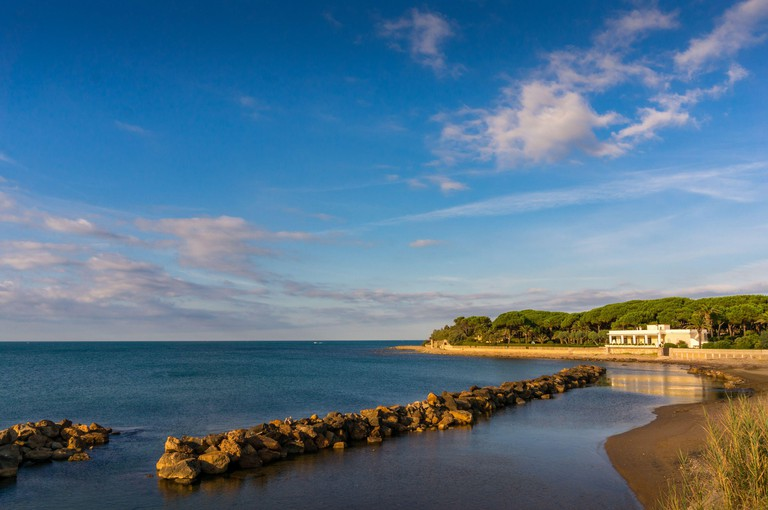 Mediterranean seascape of sea shore line with sandy beach and rock wave breaker. Santa Marinella, Italy - 2AYTNAA