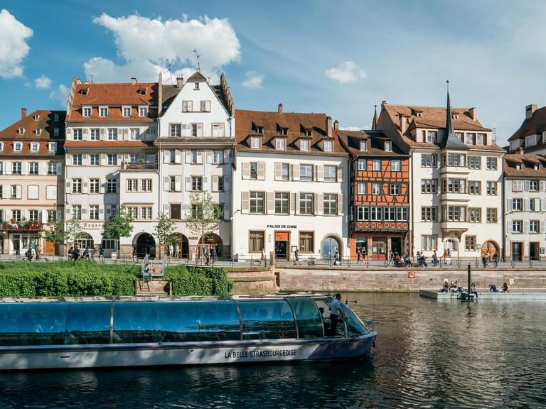 Strasbourg, France - May 5, 2019: Quai des Batelier pedestrian street in central Strasbourg with Batorama tourist boat and Alsatian architecture