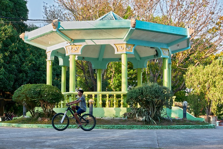 Leon, Iloilo, Philippines: Teenage boy riding a bike in front of a green colored pavilion at the town plaza park in summer time