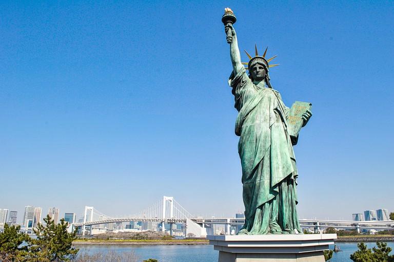Replica Statue of Liberty in Odaiba, with the Rainbow Bridge behind it.  Odaiba. Tokyo.  Japan.