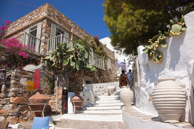 Tourist couple walking up the stairs of the old town Kastro, Sifnos, Cyclades Islands, Greek Islands, Greece, Europe