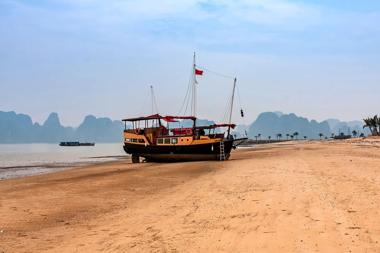 A cruise junk boat on the Halong Bay beach, Tuan Chau Island