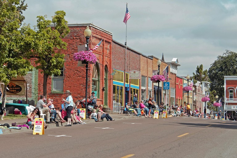 A crowd of spectators line the street of historic buildings on a sunny Summer day as they wait for the Brownsville, Oregon parade to begin.