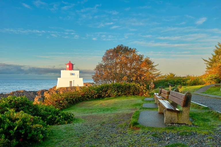 The lighthouse alongside the Wild Pacific Trail in Ucluelet is lit up by the morning sun with the Pacific Ocean and blue sky in the backround.