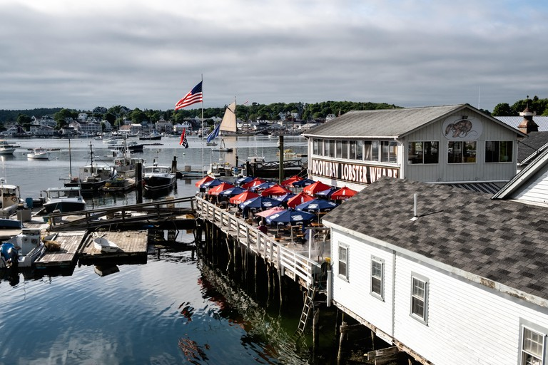 Lobster boats tied up along the docks at the Boothbay Lobster Wharf and Pound on a cloudy summer day in Boothbay Harbor Maine.