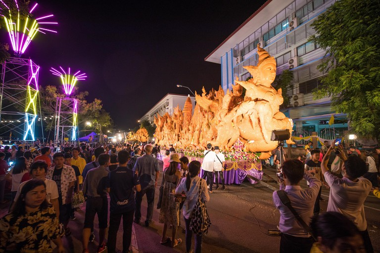 W3TNCC Ubon Ratchathani, Thailand. 17th July, 2019. Tourists watch giant wax sculptures during the candle festival in Ubon Ratchathani, Thailand, July 16, 2019. The Ubon Ratchathani Candle Festival is held to commemorate the Buddha's first sermon and mark the beginning of the Buddhist Lent. The highlight of the annual event is the parade of giant floats of wax sculptures throughout the city, each representing a local temple, a district or an institution. Credit: Zhang Keren/Xinhua/Alamy Live News