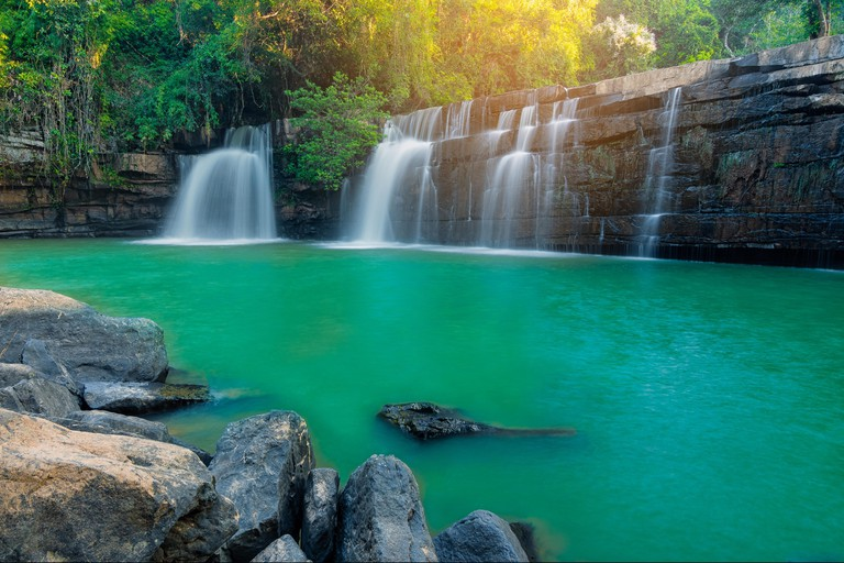 Sri Dit Waterfall is a single-level waterfall with streams flowing through the cliff and rock layer, with sunlight in jungle.
