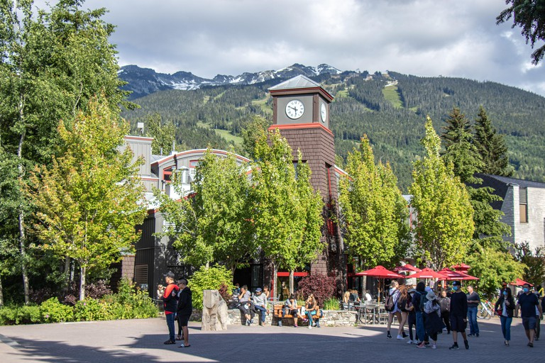 Whistler, Canada - July 5,2020: Whistler Village full of people on a sunny day with mountain view in the background. Selective focus