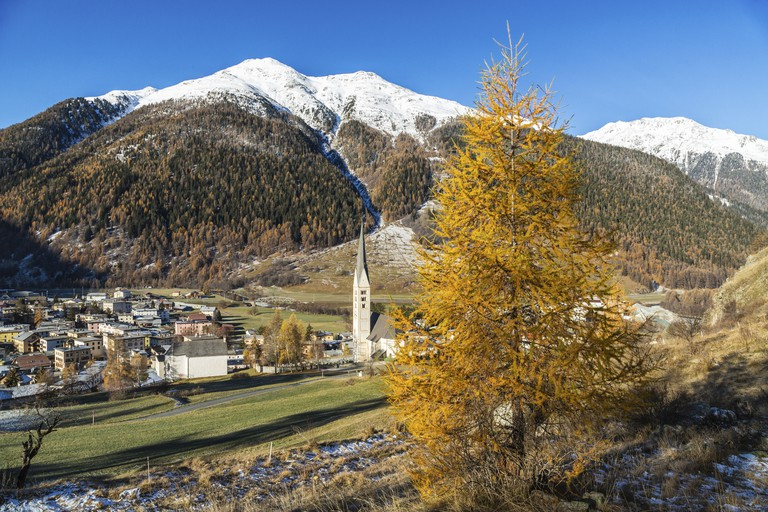 Autumn colours frame the village of Zernez surrounded by woods and snowy peaks Engadine Canton of Graubünden Switzerland Europe