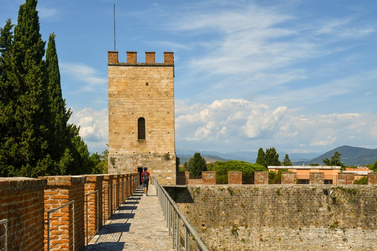 View of the elevated walkway on the ancient city walls of Pisa with a corner tower and a tourist walking from behind in summer, Tuscany, Italy