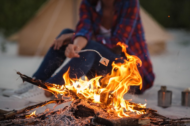 Close up photo of roasting marshmallows over the fire near tent in camping. Focus on fire. Young tourist woman having fun near the fire in the nature.