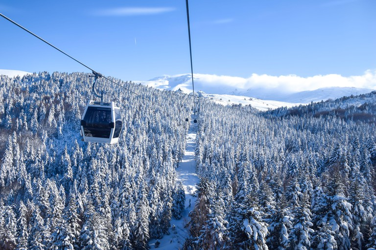 Transportation via cable car among snow covered tree on a sunny winter day in Uludag National Park, Turkey.