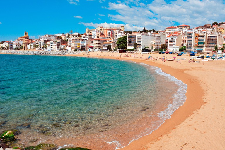 A view of Platja de les Barques beach in Sant Pol de Mar, Spain, where some people are sunbathing.