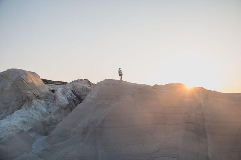 Man exploring Sarakiniko Beach in Milos, Greece at sunset