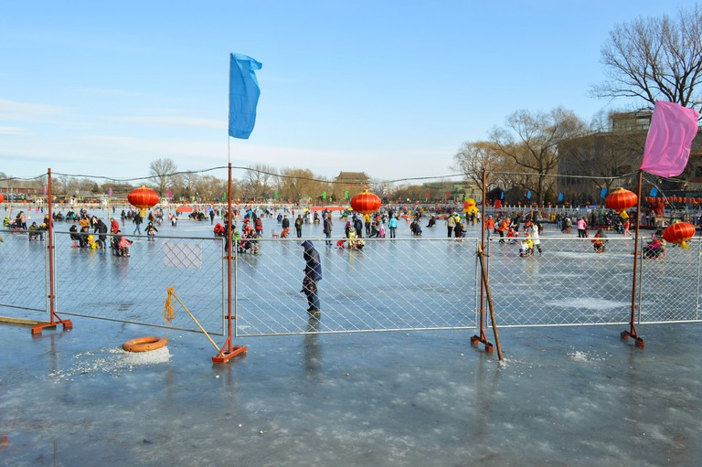 Beijing / China - January 25, 2014: People skating and sliding on sledges on frozen Houhai lake in Xicheng District in central Beijing, China
