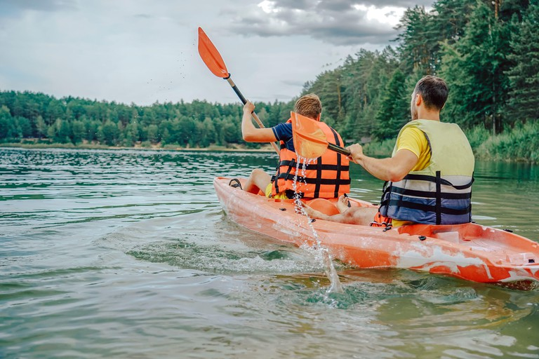 two guys in a red kayak on the river, in life jackets