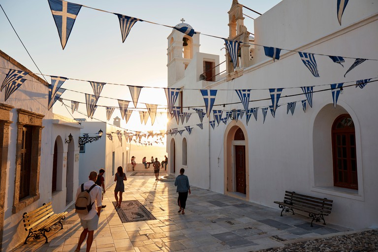Sunset in Plaka, the main town on Milos island, with Greek Orthodox feast decoration on the church square with pebble mosaic, Greece