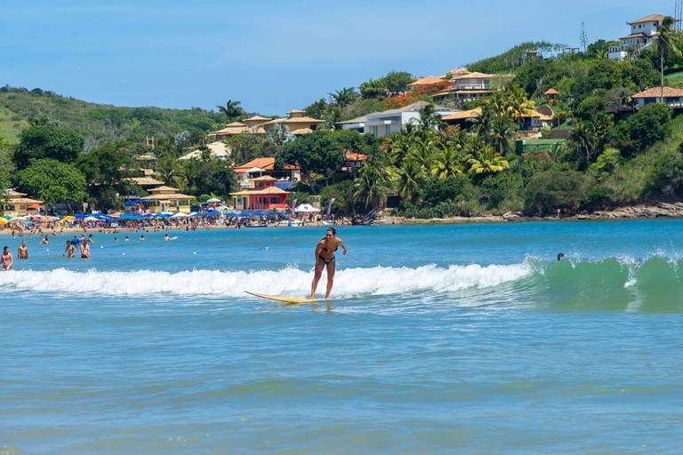 Geriba beach, Buzios, Rio de Janeiro, Brazil - December 22, 2019: Surf in south atlantic coast. Beautiful young woman doing aquatic sports in a sunny
