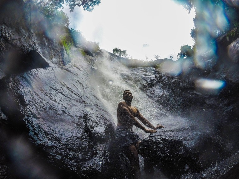 Man Leaning On Rock At Waterfall
