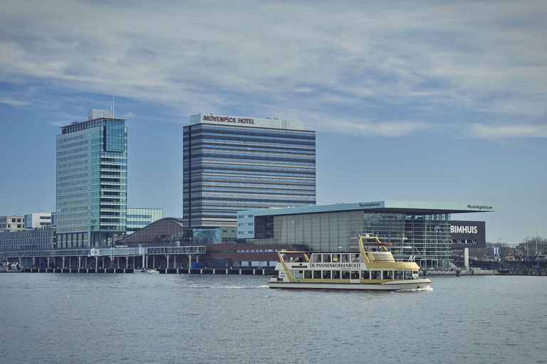 East view of the hotel, the Music Hall (Muziekgebouw) is in the front of the building. The Pancake Boat (De Pannenkoekenboot) is on the Ij river