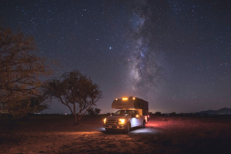 A small pickup RV is on a camping spot under the Milky Way