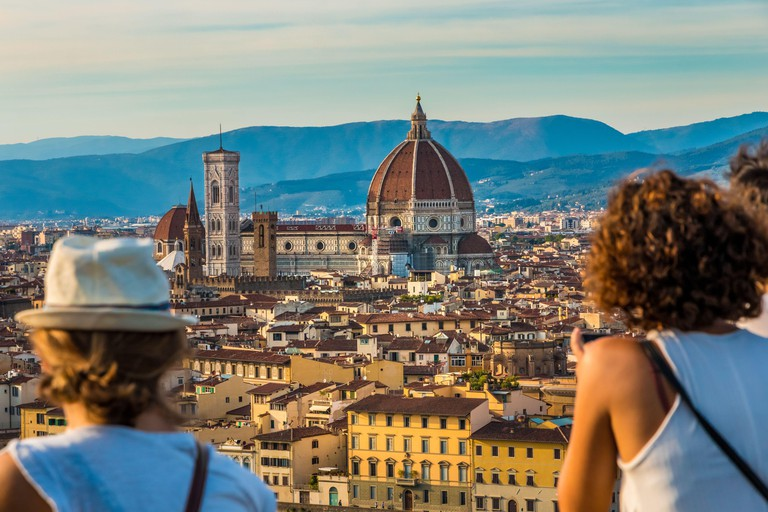 Two women admiring the panoramic view from the square Piazzale Michelangelo to the historic heart of Florence with the Cathedral Santa Maria del Fiore...