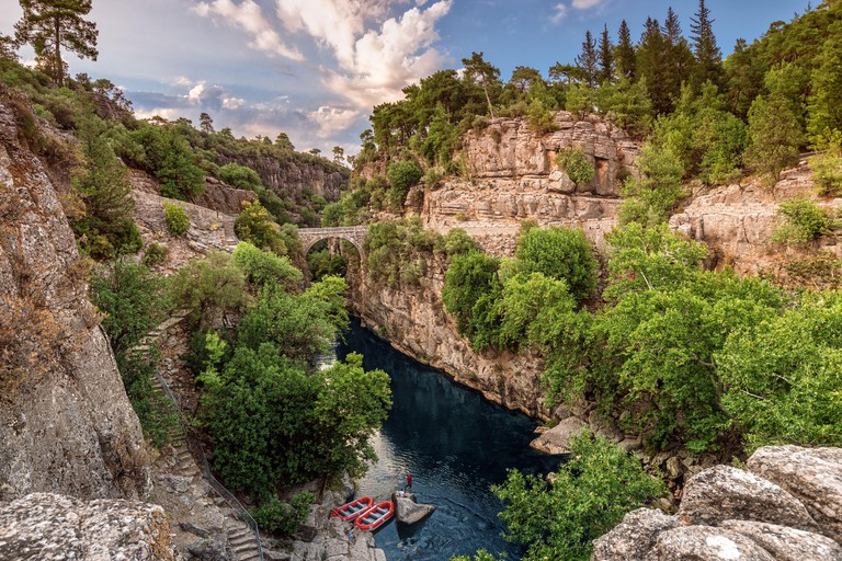Ancient arch bridge over the Koprucay river gorge in Koprulu national Park in Turkey. Panoramic scenic view of the canyon and blue stormy mountain riv