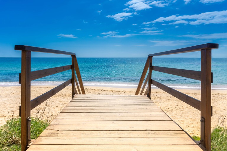 Boardwalk to sandy beach. Wooden walkway over sand to sea. Sunny beach with wooden walk floor. Vacation background. Summer vacation concept. Copy spac