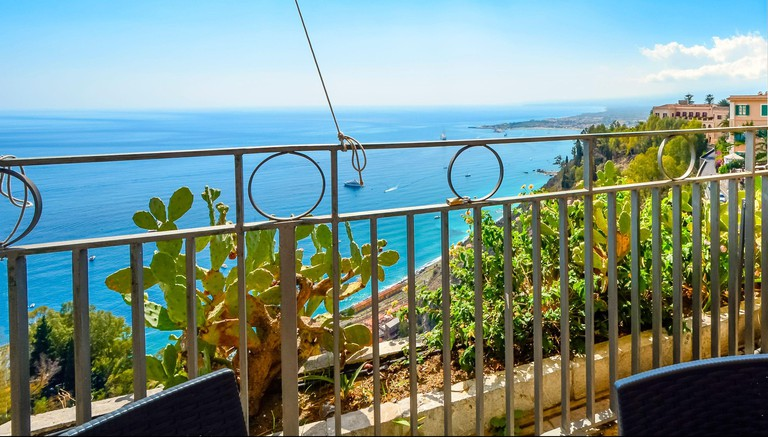 View from a hillside cafe's covered patio seating of the Mediterranean sea and coastline of Taormina, Italy, on the island of Sicily.