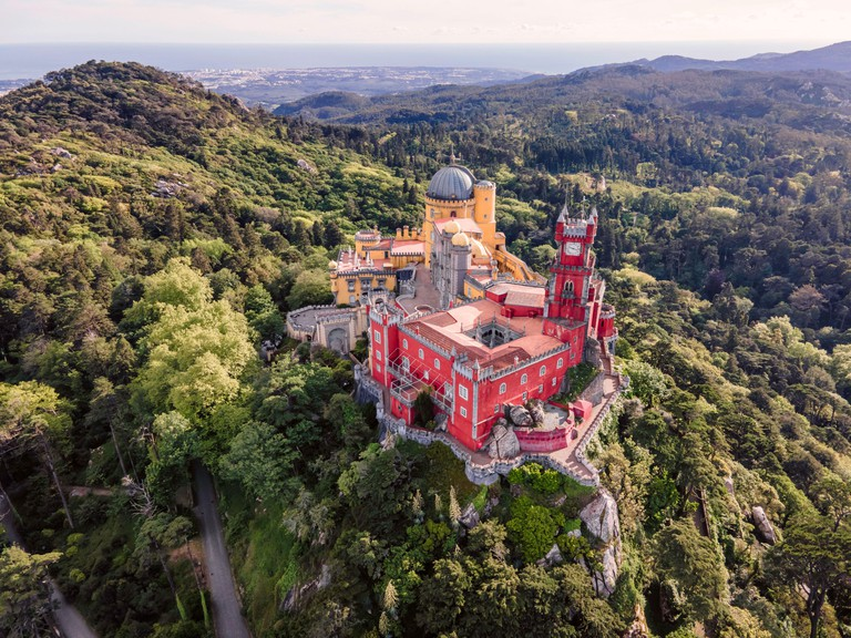 Aerial view of Pena Palace, a colourful Romanticist castle building on hilltop during a beautiful sunset, Sintra, Lisbon, Portugal. - 2FN07X2
