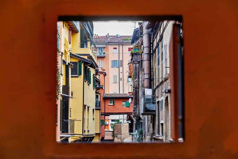 2G563KK Secret window in the wall to the hidden part of the city in Bologna, Italy. Canal of Reno in Piella street